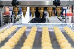 Feche acima da massa ou do creme e proveja de bocal a descarga do biscoito ou dos doces automáticos que fazem a máquina na linha  imagens de stock
