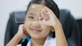Feche acima da menina asiática do tiro no uniforme tailandês do estudante do jardim de infância usando o vidro dos cleas mesmos c vídeos de arquivo