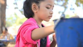 Feche acima da menina asiática do tiro que pinta a boneca filme