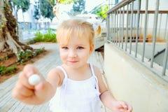 Feche acima da menina blondy pequena bonito da criança no vestido branco que dá doces redondos doces pequenos para você Foco sele fotografia de stock
