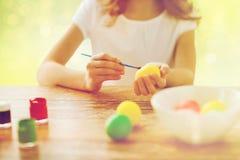 Feche acima da menina com os ovos da páscoa da coloração da escova Fotos de Stock