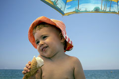 Feche acima da menina de sorriso adorável do retrato que come o gelado na praia Foto de Stock Royalty Free