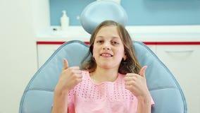 Feche acima da menina feliz que dá os polegares acima após a verificação dental acima video estoque