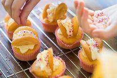 Feche acima da menina na cozinha que decora queques em casa feitos Foto de Stock Royalty Free