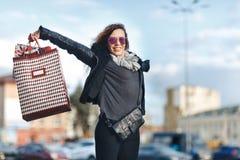 Feche acima da menina nova do moderno do retrato do estilo de vida da forma, com sacos de compras andando para fora da loja Imagens de Stock