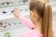 Feche acima da menina que escolhe vidros na loja do sistema ótico foto de stock