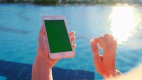 Feche acima da menina que usa a tela do verde do telefone celular ao relaxar perto da piscina Mãos que guardam o cromo do smartph video estoque