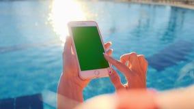 Feche acima da menina que usa a tela do verde do telefone celular ao relaxar perto da piscina Mãos que guardam o cromo do smartph filme