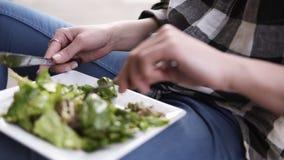 Feche acima da metragem de uma mulher nova, atrativa aprecia seu alimento delicioso Roupa ocasional dentro vídeos de arquivo