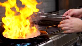 Feche acima da metragem do cozinheiro que frita a carne do peito de pato com chama aberta vídeos de arquivo