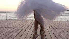 Feche acima da metragem dos pés novos do ` s da bailarina no movimento da dança Dançarino de bailado no exercício branco longo do filme