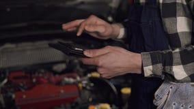 Feche acima da metragem no movimento lento do auto técnico do serviço que usa a tabuleta digital para examinar as edições do veíc video estoque