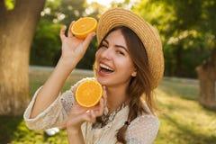 Feche acima da moça bonita no tempo da despesa do chapéu do verão no parque, imagens de stock