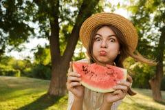 Feche acima da moça engraçada no tempo da despesa do chapéu do verão no parque, foto de stock