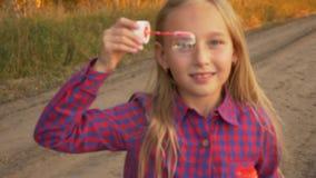 Feche acima da moça da vista que olha através da sabão-bolha fora De primeiro plano unfocused a focalizar vídeos de arquivo