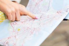 Feche acima da mão da mulher que aponta o dedo ao mapa Imagens de Stock Royalty Free