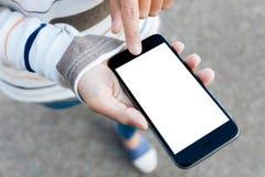 Feche acima da mão da mulher usando o telefone que anda na rua exterior Imagens de Stock