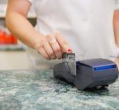 Feche acima da mão humana que põe o cartão de crédito na máquina do pagamento Fotografia de Stock Royalty Free