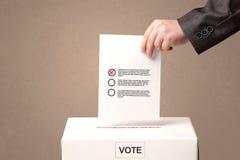 Feche acima da mão masculina que põe o voto em uma urna de voto Fotografia de Stock Royalty Free