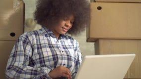 Feche acima da mulher africana com um penteado afro que senta-se no assoalho e que usa um port?til filme