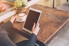 Feche acima da mulher asiática da mão que usa o tablet pc na cafetaria w Imagens de Stock