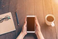 Feche acima da mulher asiática da mão que usa o telefone na cafetaria e no sunligh Imagem de Stock Royalty Free