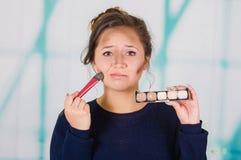 Feche acima da mulher bonita nova que guarda uma paleta compor e que faz a composição louca em sua cara usando uma escova, na Fotos de Stock