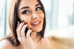 Feche acima da mulher bonita que fala o telefone celular e pelo sorriso fotografia de stock