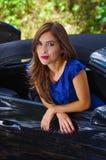 Feche acima da mulher bonita que veste um vestido azul e que levanta dentro de um carro preto luxuoso em um roadtrip a posição do Fotos de Stock
