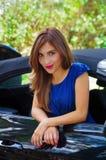 Feche acima da mulher bonita que veste um vestido azul e que levanta dentro de um carro preto luxuoso em um roadtrip a posição do Foto de Stock Royalty Free