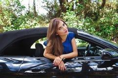 Feche acima da mulher bonita que veste um vestido azul e que levanta dentro de um carro preto luxuoso em um roadtrip a posição do Imagem de Stock