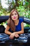 Feche acima da mulher bonita que veste um vestido azul e que levanta dentro de um carro preto luxuoso em um roadtrip a posição do Fotografia de Stock Royalty Free