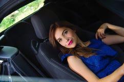 Feche acima da mulher bonita que veste um vestido azul em um assento reclinado e que levanta dentro de um carro preto luxuoso na Fotos de Stock Royalty Free
