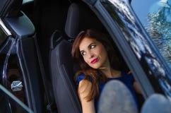 Feche acima da mulher bonita que veste um vestido azul em um assento reclinado e que levanta dentro de um carro preto luxuoso na Foto de Stock Royalty Free