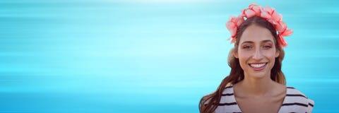 Feche acima da mulher com as flores no cabelo contra o fundo azul obscuro Foto de Stock