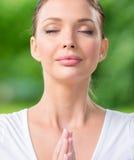 Feche acima da mulher com gesticular fechado da oração dos olhos Imagem de Stock