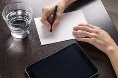 Feche acima da mulher com tabuleta e escreva um papel na tabela de madeira fotos de stock royalty free