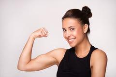 Feche acima da mulher da raça misturada que demonstra o bíceps fotografia de stock