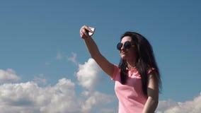Feche acima da mulher de sorriso nova que faz o selfie Emoção positiva e dia de verão ensolarado Fundo azul do céu nebuloso video estoque