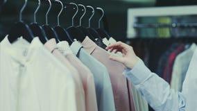 Feche acima da mulher está tocando em ganchos com as blusas na sala de exposições filme