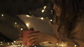 Feche acima da mulher feliz nova que toma seu presente de Natal na sala decorada Natal As luzes de Natal cercam-na