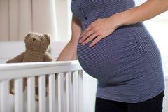 Feche acima da mulher gravida que põe o mamadeira de Teddy Bear Into Cot In fotos de stock royalty free