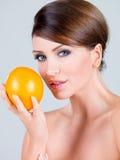 Feche acima da mulher lindo que guarda o fruto alaranjado imagem de stock