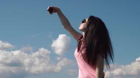 Feche acima da mulher moreno do encanto que faz o selfie Emoção positiva e dia de verão ensolarado Fundo azul do céu nebuloso vídeos de arquivo