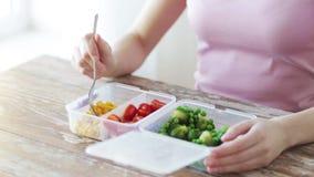 Feche acima da mulher que come vegetais do recipiente filme