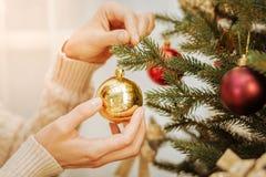Feche acima da mulher que decora a árvore para o Natal imagens de stock