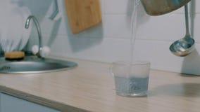 Feche acima da mulher que derrama a água quente sobre o saquinho de chá no copo de vidro transparente no movimento lento video estoque