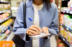 Feche acima da mulher que escreve ao bloco de notas no mercado Foto de Stock