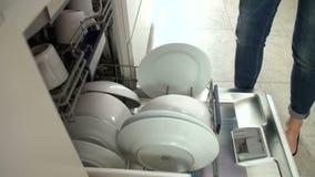 Feche acima da mulher que esvazia a louça da máquina de lavar louça vídeos de arquivo