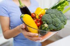 Feche acima da mulher que guarda vegetais na bacia Imagem de Stock Royalty Free